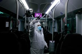 Le 11 mai, des employés des CFL surprotégés désinfectent méticuleusement un bus. ((Photo: Matic Zorman / Maison Moderne))