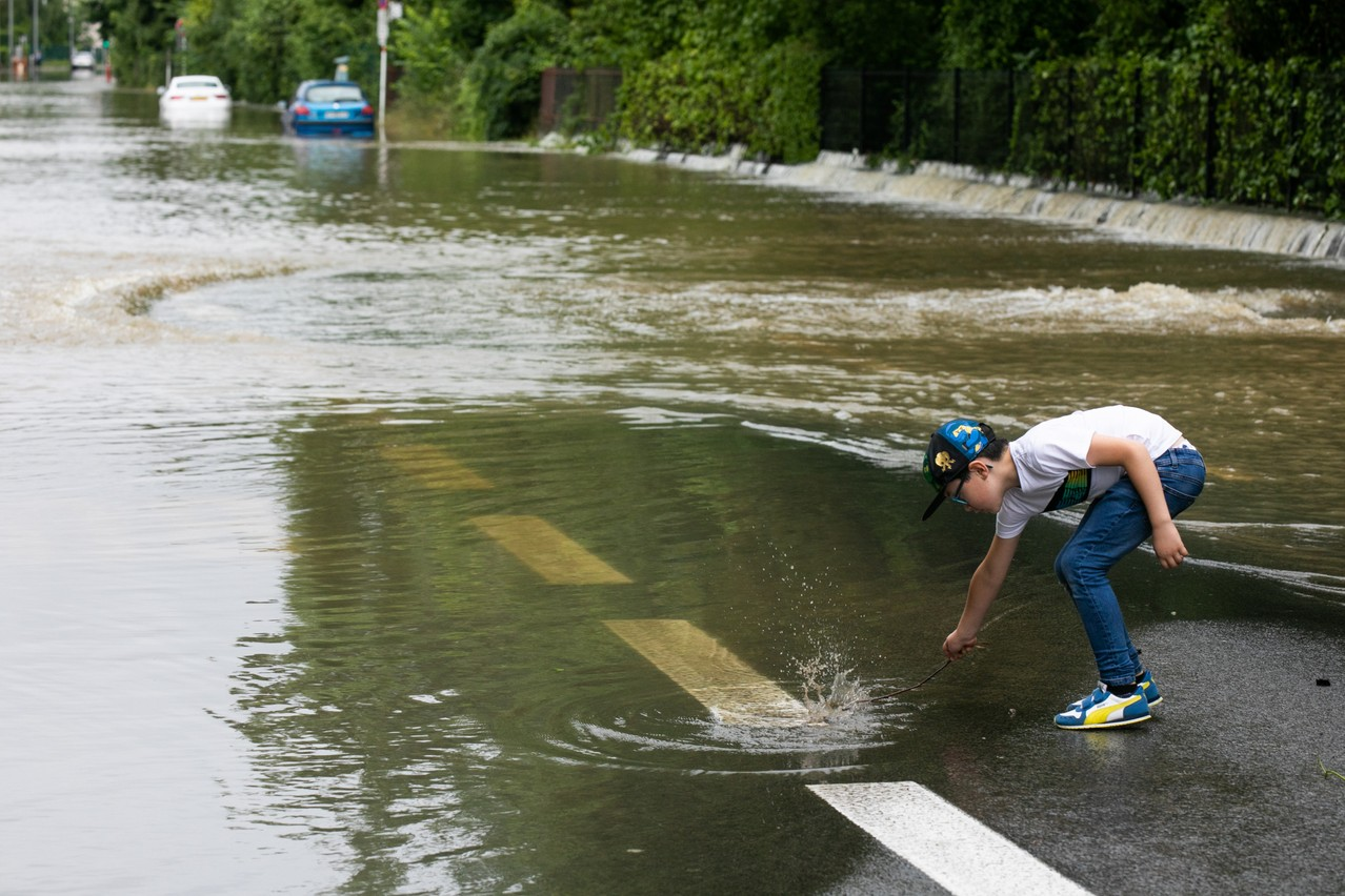 A 15 July photo shows a child next to a flooded Rue de Beggen Photo: Matic Zorman / Maison Moderne