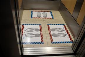 Dans l'ascenseur, des marquages au sol permettent de placer les personnes à trois maximum et dos à dos. ((Photo: Matic Zorman / Maison Moderne))
