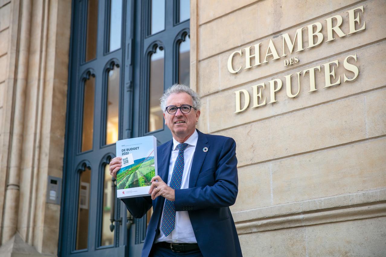 Finance minister Pierre Gramegna holding the 2022 draft budget outside the Chamber of Deputies Photo: Romain Gamba / Maison Moderne
