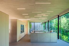 Dans l'espace ouvert de la cuisine, des profils intégrés au plafond créent un effet graphique qui répond également aux différents besoins d'utilisation de l'espace, un lustre éclaire directement la table, et des lumières indirectes sur un bloc central confèrent une lumière d'ambiance. ((Photo: Steve Troes))