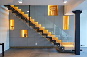 L'éclairage fonctionnel vers les marches de l'escalier reste caché derrière l'habillage, souligne l'architecture intérieure réalisée par NJOY et se conjugue harmonieusement avec l'éclairage plus chaud des niches. ((Photo: Christof Weber))