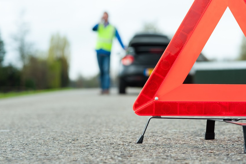Warning triangle seen in front of a broken down car, with driver wearing yellow safety vest calling for assistance Fotosenmeer/Shutterstock