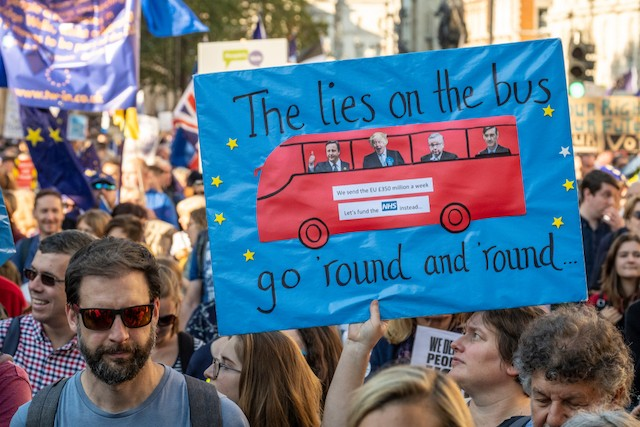 """A woman holds a banner during the 20 October 2018 people's vote march demanding a second referendum on Brexit. """"The lies on the bus go round and round"""" refers to Boris' Brexit bus claiming the UK gives £350m per week to the EU, money which claimed could be spent on the NHS. Shutterstock"""