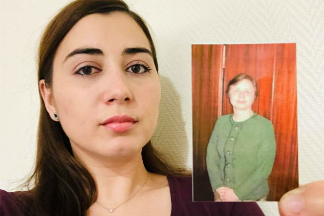 Journalist Roxana Mironescu holds a photo of her school Latin teacher, Valeria Socaciu Roxana Mironescu