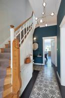 Dans l'entrée, on trouve des éléments historiques de la maison, comme les carreaux de ciment ou le garde-corps en bois travaillé de l'escalier. ((Photo: Andrés Lejona/Maison Moderne))