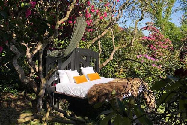 La«belle étoile» et son lit déposé en pleine nature, sous les rhododendrons. (Photo: Domaine de Ronchinne)