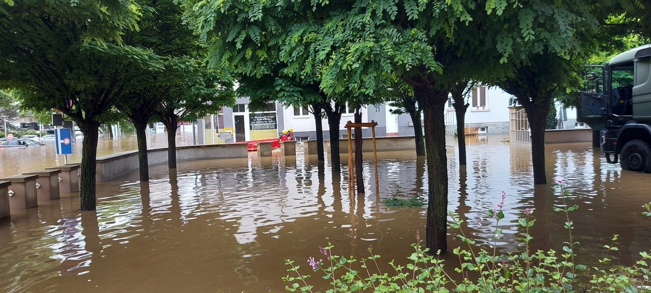 A 15 July 2021 photo shows helpers pulling a boat along a flooded street in front of the CNL in Mersch Photo: CNL