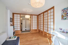 Au rez-de-chaussée, un espace à l'esprit minimaliste sert de pièce multifonctionnelle. Derrière des parois coulissantes d'inspiration japonaise se dissimulent buanderie, chambres des enfants, placards… ((Photo: Andrés Lejona/Maison Moderne))