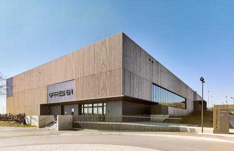 Le centre sportif présente un volume compact recouvert d'un bardage en lamelles de bois verticales. (Photo: Andrés Lejona/Maison Moderne)