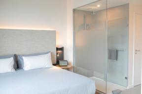 Les douches ne sont séparées du lit que par une paroi vitrée. ((Photo: Matic Zorman / Maison Moderne))