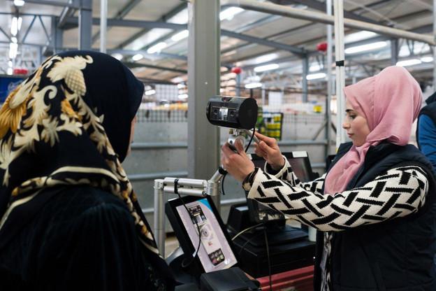La petite machine, comme un radar, scanne l'iris de la cliente (ici, de dos), et son porte-monnaie électronique est débité. Sans papiers d'identité ni carte de crédit ou cash. (Photo: WFP)
