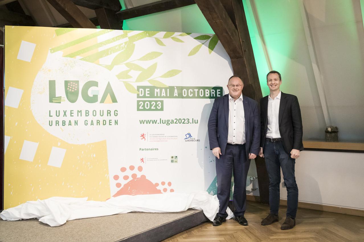 Romain Schneider, ministre de l'Agriculture, de la Viticulture et du Développement rural, et Serge Wilmes, 1er échevin de la Ville de Luxembourg devant la nouvelle identité visuelle de la Luga 2023. (Photo: Caroline Martin)