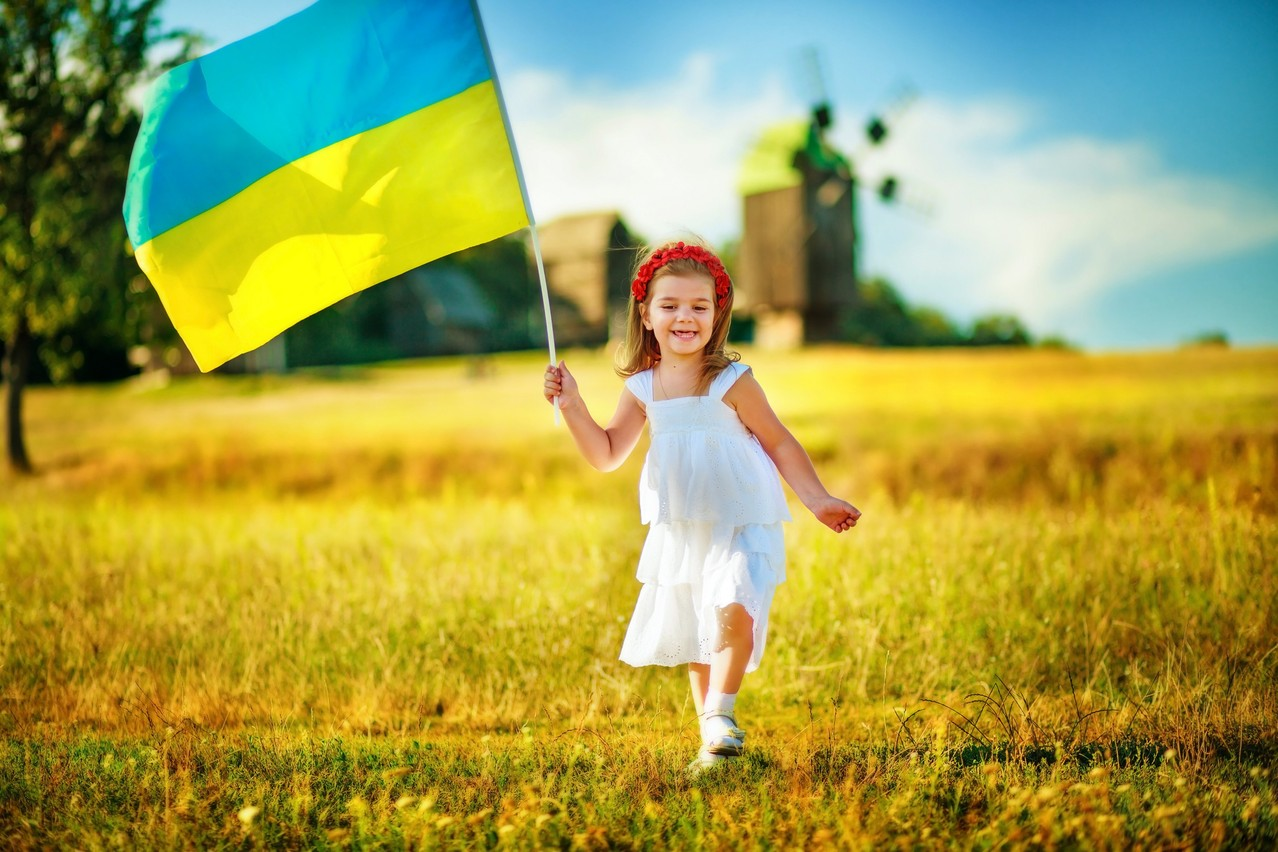 Child carries fluttering blue and yellow flag of Ukraine against background of mills in Pirogovo. (c) 2017 Lipatova Maryna/Shutterstock.