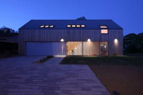 La façade se compose de lamelles en bois traitées comme une façade rideau. ((Photo: Morph4))