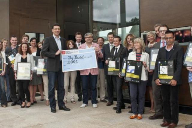 Mike Koedinger (Maison Moderne), a remis un chèque de 50.000 euros à Pit Wolff (Energieagence), représentant de MyClimateLux. (Photo : Éric Chenal /Blitz)