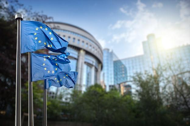 European Union flag against parliament in Brussels, Belgium. (Photo: artJazz)