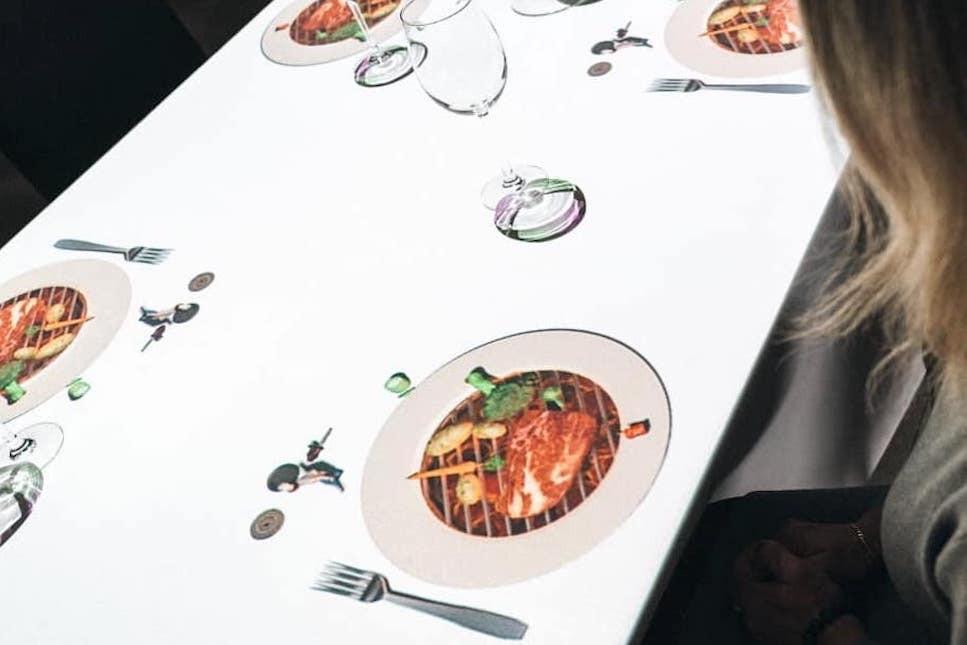 Projeté sur la table, Le Petit Chef annonce la suite du repas avec humour. (Photo: Le Petit Chef)