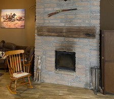 Au-dessus de la cheminée, une tête de caribou et une Winchester. Le luxe du détail pour qui aurait envie de somnoler sur le rocking-chair. ((Photo: Shutterstock))