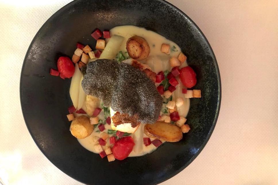 Le sébaste aux asperges luxembourgeoises, caché sous une chips à l'encre de seiche travaillée comme un krupuk, réalisé par le chef Yves Van Dorpe au Château d'Urspelt. (Photo: Maison Moderne)