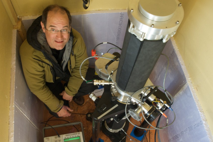 Dr Francis poses with one of his gravimeters, which is housed in a little hut in Antarctica. Photo: Olivier Francis
