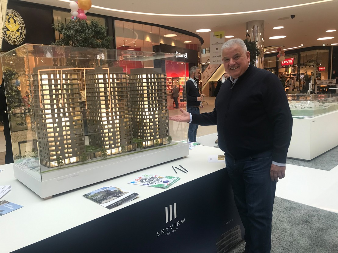 Flavio Becca in front of the model of the Skyview Trilogy residential towers presented at the Move fair in the Cloche d'Or shopping centre. Photo: Maison Moderne